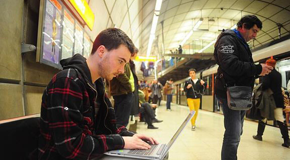 Young man uses a laptop computer at a busy train or subway station.