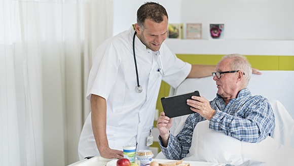 Hospital patient sharing something on his tablet screen with a nurse