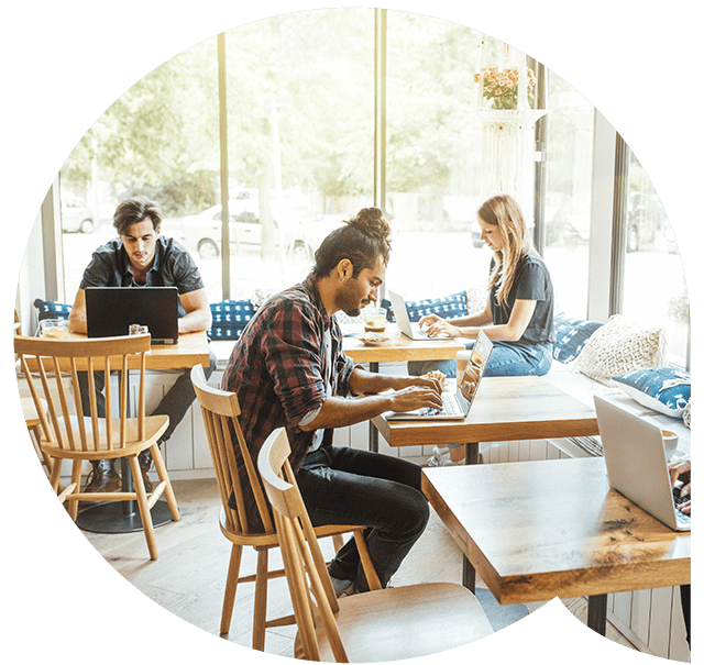 Young people working on laptops at a sunny café