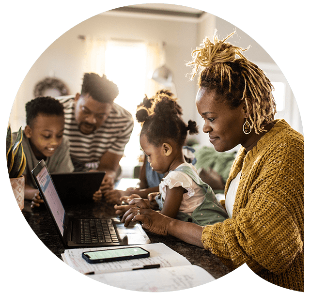 Family with children gathered around the devices doing homework