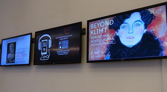 Wall mounted monitors display custom art gallery advertisements and information in BOZAR