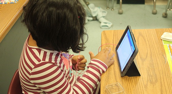 A student using a tablet in a classroom