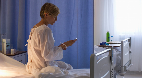 Hospital patient uses a mobile phone