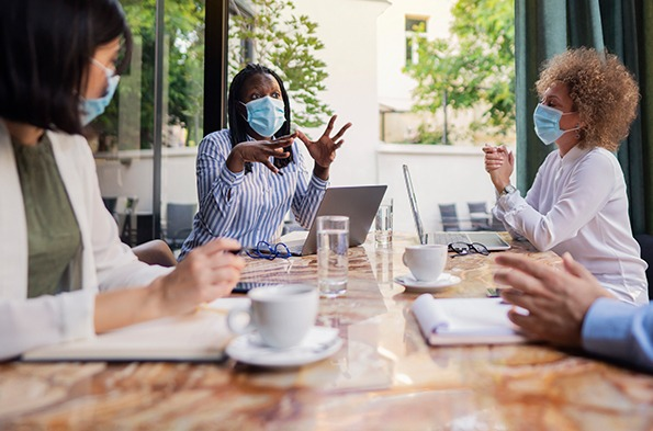 Office workers wearing masks in a meeting