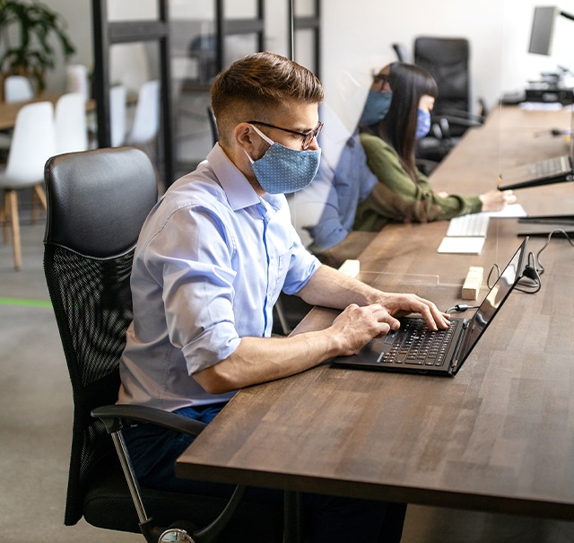 Masked personnel working at an office with an open plan