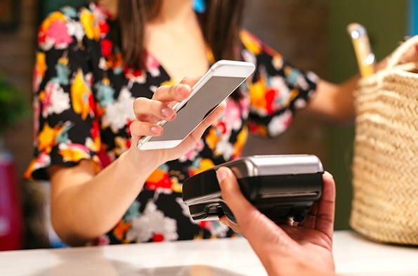 Customer using a mobile phone at a checkout