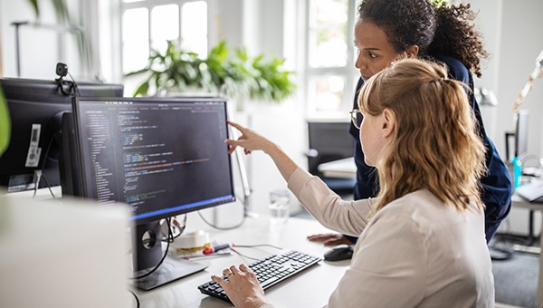 Two engineers reviewing code on a screen