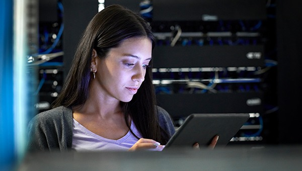 A female engineer working on a tablet in front of a server rack