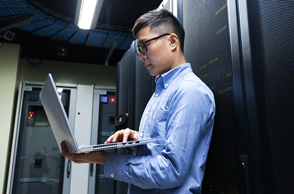 Network engineer holding a laptop at a data center