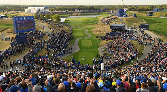 Crowds in the stands of Ryder Cup Europe point their mobile phones towards the course