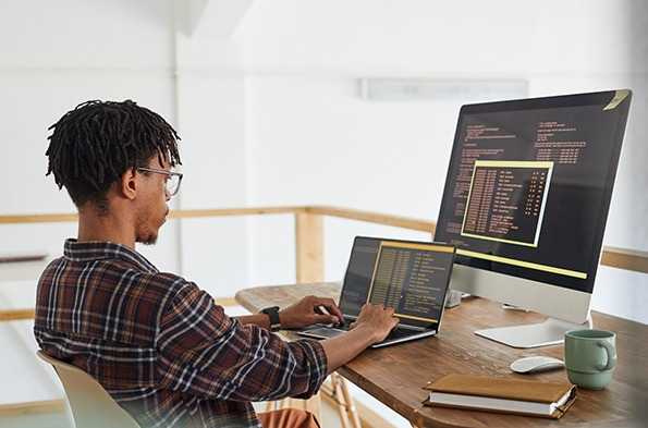 Network administrator in front of a laptop and a monitor
