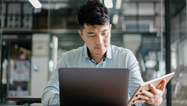Tech worker behind a laptop referring to something on a tablet