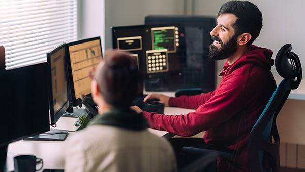 IT professionals in front of multiple screens