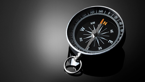 Black and silver compass on a black surface