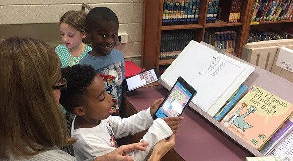 School kids & their teacher interact with a tablet in the library